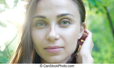 Close-up view of the beautiful face of a young girl who poses for a photograph. The face of a pretty girl with green eyes who smiles at the camera in warm sunny weather against a background of trees.