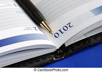 Close up view of the diary with a pen isolated on blue