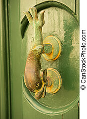 Close-up view of the fish shaped knocker on a green door