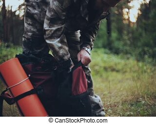 Close-up view of the man packing the backpack on the meadow in forest. Male in camouflage walking in the nature alone.