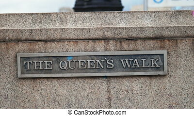 Close up 4k View of a metal plaque with the words The Queens Walk, with a small blue paint stain above the letter U, on a concrete wall alongside a promenade