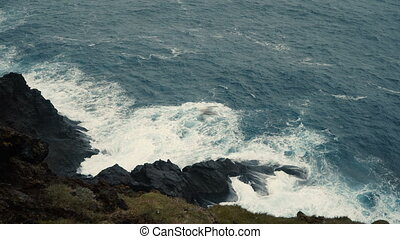 Close-up view of the sea. Waves with foam splashing on the shore, on black rocks.