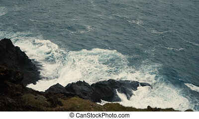 Close-up view of the shore of the blue sea in sunny day. Waves splashing on the black rocks.