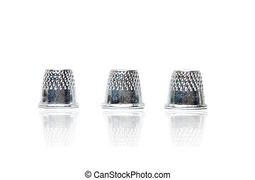 Close up view of three silver thimbles isolated on a white background.