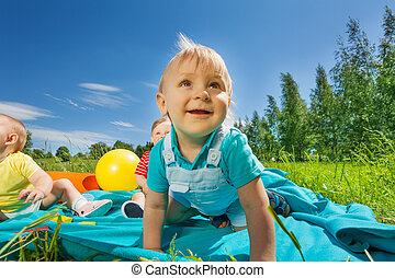 Close-up view of toddlers sitting on blanket