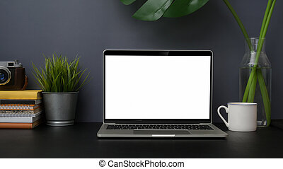 Close up view of trendy photographer workplace with mock up laptop on black table with grey wall