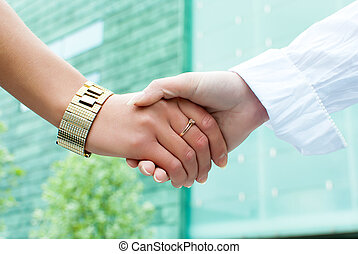 Close up view of two women shaking hands outdoors
