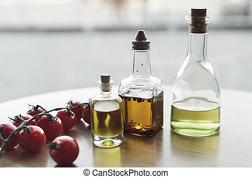 close up view of various types of oil in bottles and fresh cherry tomatoes