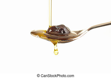 Close up view of virgin olive oil pouring on stainless stell spoon on white background