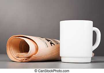 white cup and folded newspaper - close-up view of white cup ...