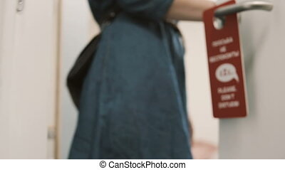Close-up view of woman comes out from the apartment and changes the knob on door hanger, asking to clean the room.