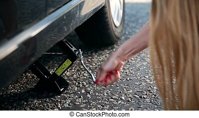 Close up view of woman's arm jacking up her car to change...