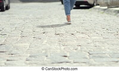 Close up view of womans legs walking on paving stones.