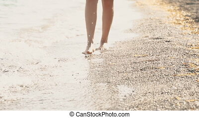 Close-up view of woman's legs walking on the pebble beach.