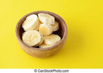 Close up view of wooden bowl with banana slices