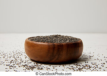 close up view of wooden bowl with chia seeds on white surface