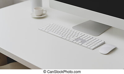 Close up view of workspace with computer, copy space and coffee cup on white table