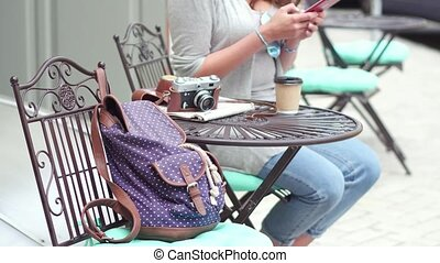 Close up view of young attractive travel girl having rest at street cafe after long walk.