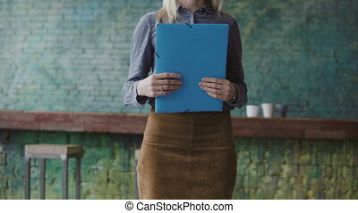 Close-up view of young blonde female holding the documents. Woman manager working in modern trendy office.