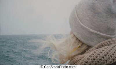 Close-up view of young blonde woman traveling on ship....