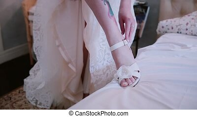 Close-up view of young bride with tattoo on the leg puts on the wedding shoes. Morning preporation before ceremony.