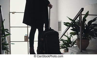 Close-up view of young businesswoman with suitcase. Traveler...
