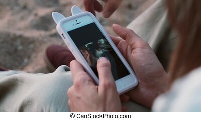 Close-up view of young couple sitting on the beach, on the sand and looking photos on smartphone, using touchscreen.