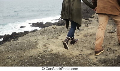 Close-up view of young couple walking on the edge of the cliff near the sea. Man and woman holding hands, romantic date.