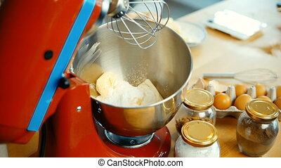 Close-up view of young female preparing dough in the bowl. Woman turns on the mixer for blending ingredients.