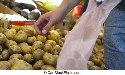 Close up view of young man buys the potatoes at the fruit market