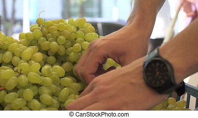 Close up view of young man hands choosing the grapes at the fruit market