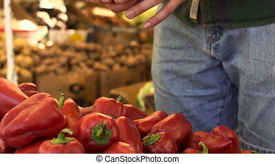 Close up view of young man hands choosing the pepper at the fruit market