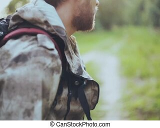Close-up view of young man with backpack looking around in forest. Male in camouflage unionalls exploring the territory.