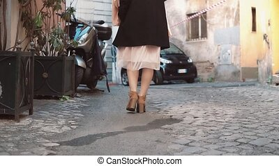 Close-up view of young stylish woman walking on cobblestone pavement road. Girl going through the street. Slow motion.