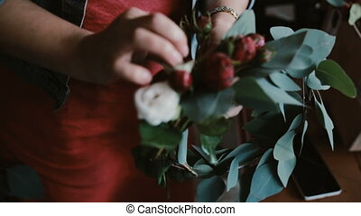 Close-up view of young woman florist making a beautiful flower composition. The decorator makes a wreath.