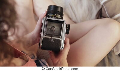 Close-up view of young woman in pajamas holds old photocamera. Multiracial couple taking photos, man poses.