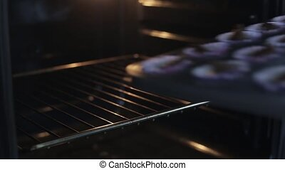 Close-up view of young woman open the oven and puts on the baking dish with dough. Female cooking the cupcakes.