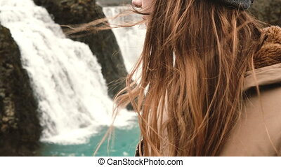 Close-up view of young woman standing near a powerful waterfall in Iceland, hair waving on the wind.