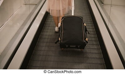 Close-up view of young woman with suitcase standing on the escalator in airport. Hipster female ready to going to trip.