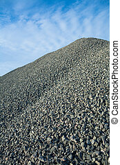 close up view on big pile of gray gravel on background of blue sky