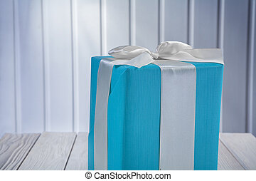 close up view on blue gift box with white ribbon on wooden board