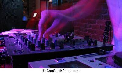 Close-up view on DJ panel during party in nightclub, time...
