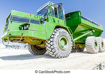 Close up view on dumper truck while he is passing over construction site. Low angle view