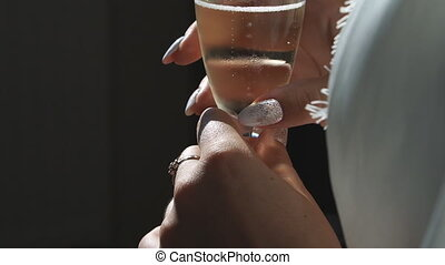 Close up view on female hand holding glass of cold champagne. Unrecognizable bride enjoying fresh alcohol beverage. Woman having leisure with glass of sparkling drink. Holiday or celebration concept.
