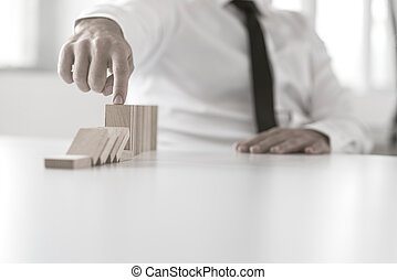 Close up view on hand of business man stopping falling blocks