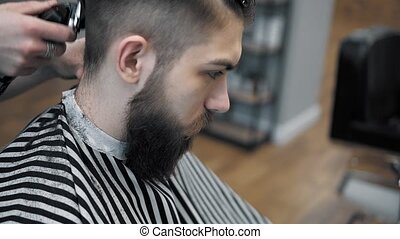 Close-up view on male's hairstyling in a barber shop with...
