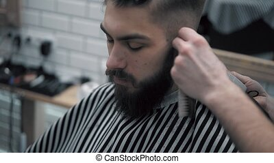 Close-up view on male's hairstyling in a barber shop with professional trimmer. Man's haircutting at hair salon with electric clipper. Grooming the hair.