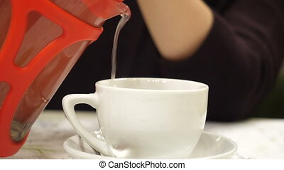 Close-up view on pouring hot tea in white cup.