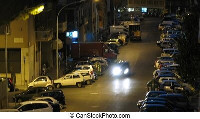 Close-up view on vehicle and human traffic at street of Rome at night