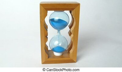Close-up view on little wooden sandglass running, time lapse
